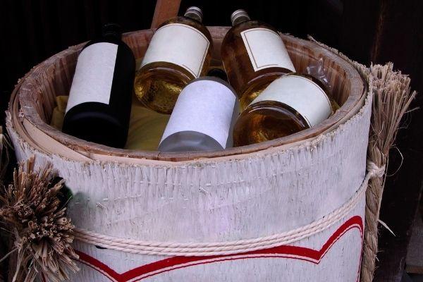 bottles of sake in open wooden sake barrel